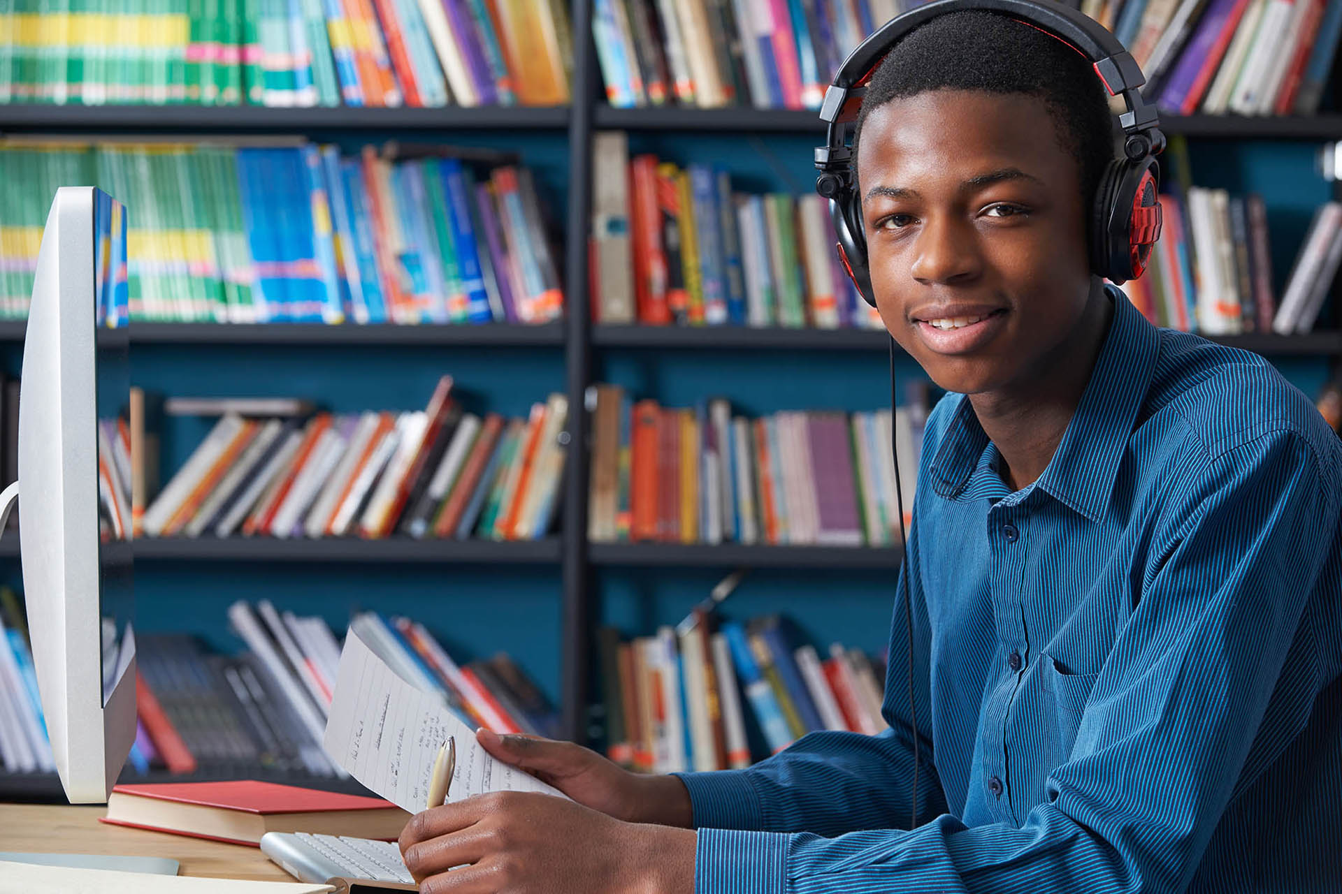 Male Teenage Student Working At Computer Wearing Headphones