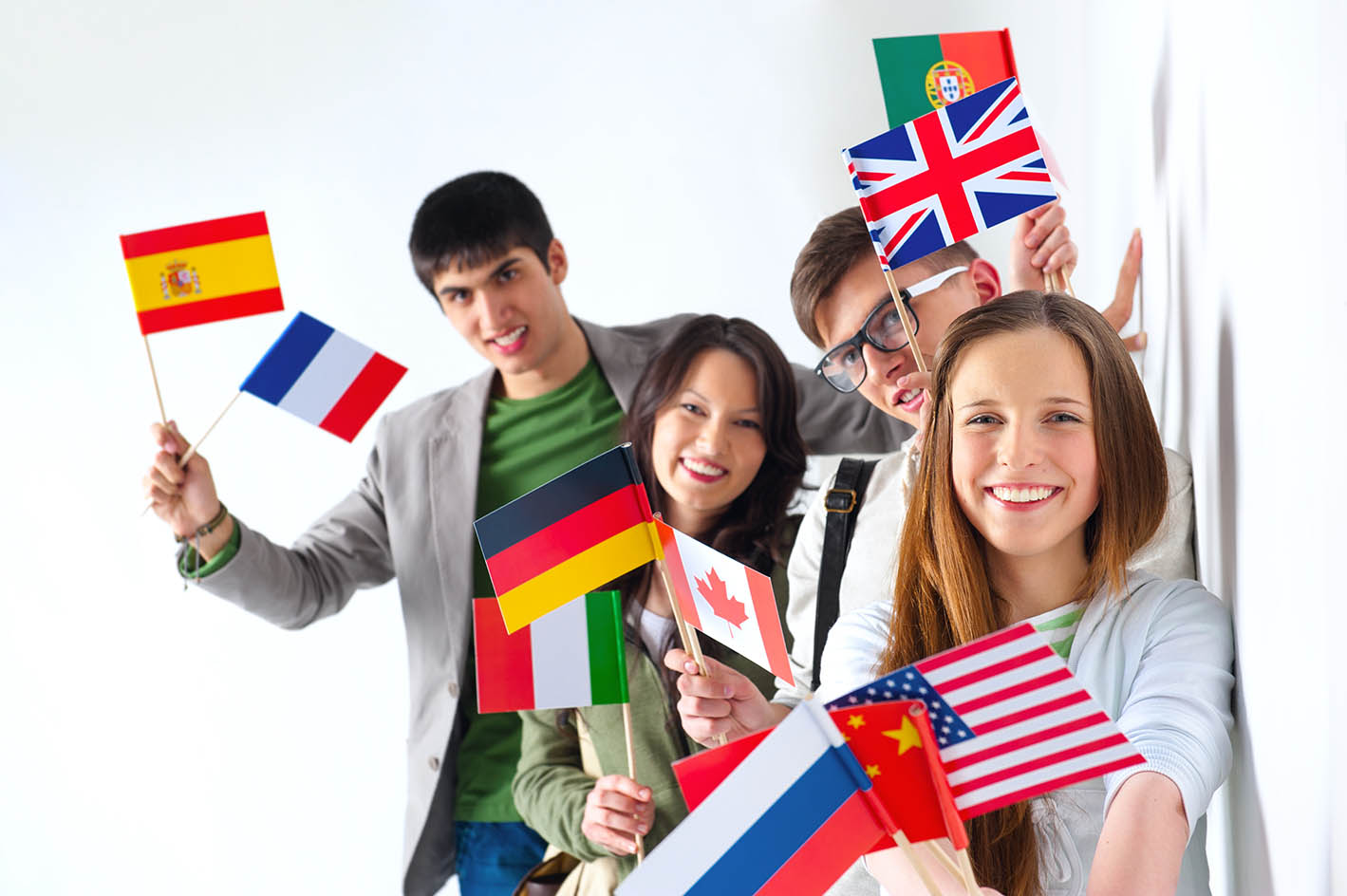 Group of cheerful happy students holding international flags and looking at camera leaning on white wall at campus. International education concept