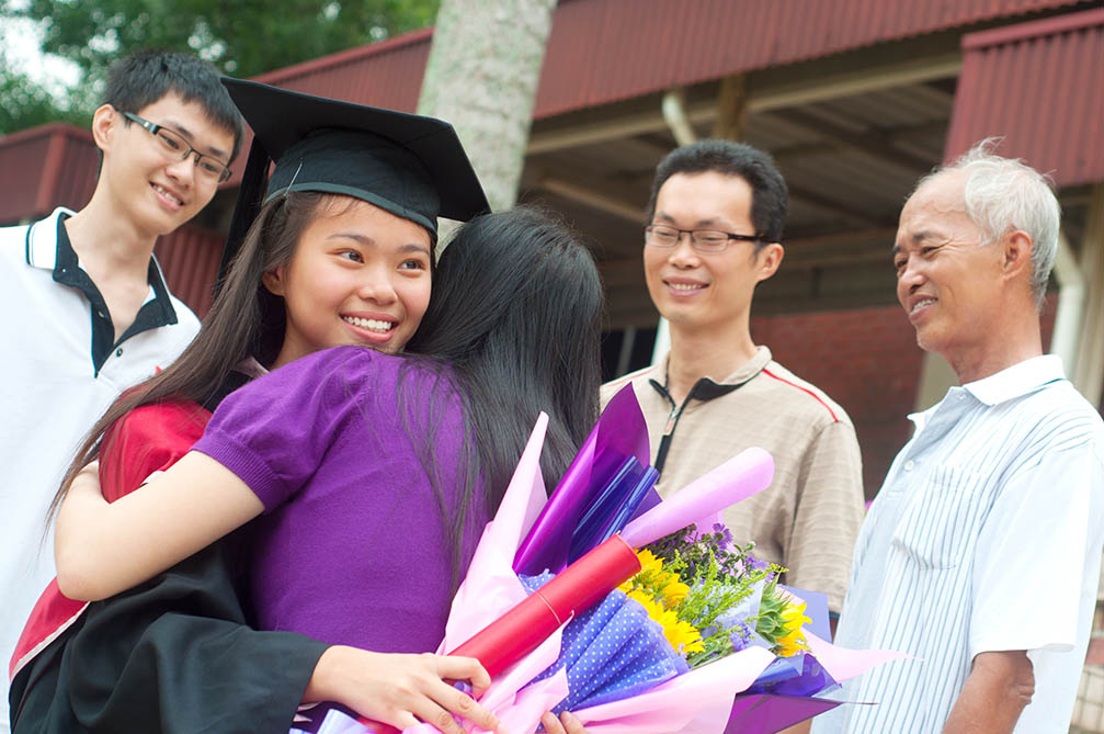 Asian university student and family celebrating graduation