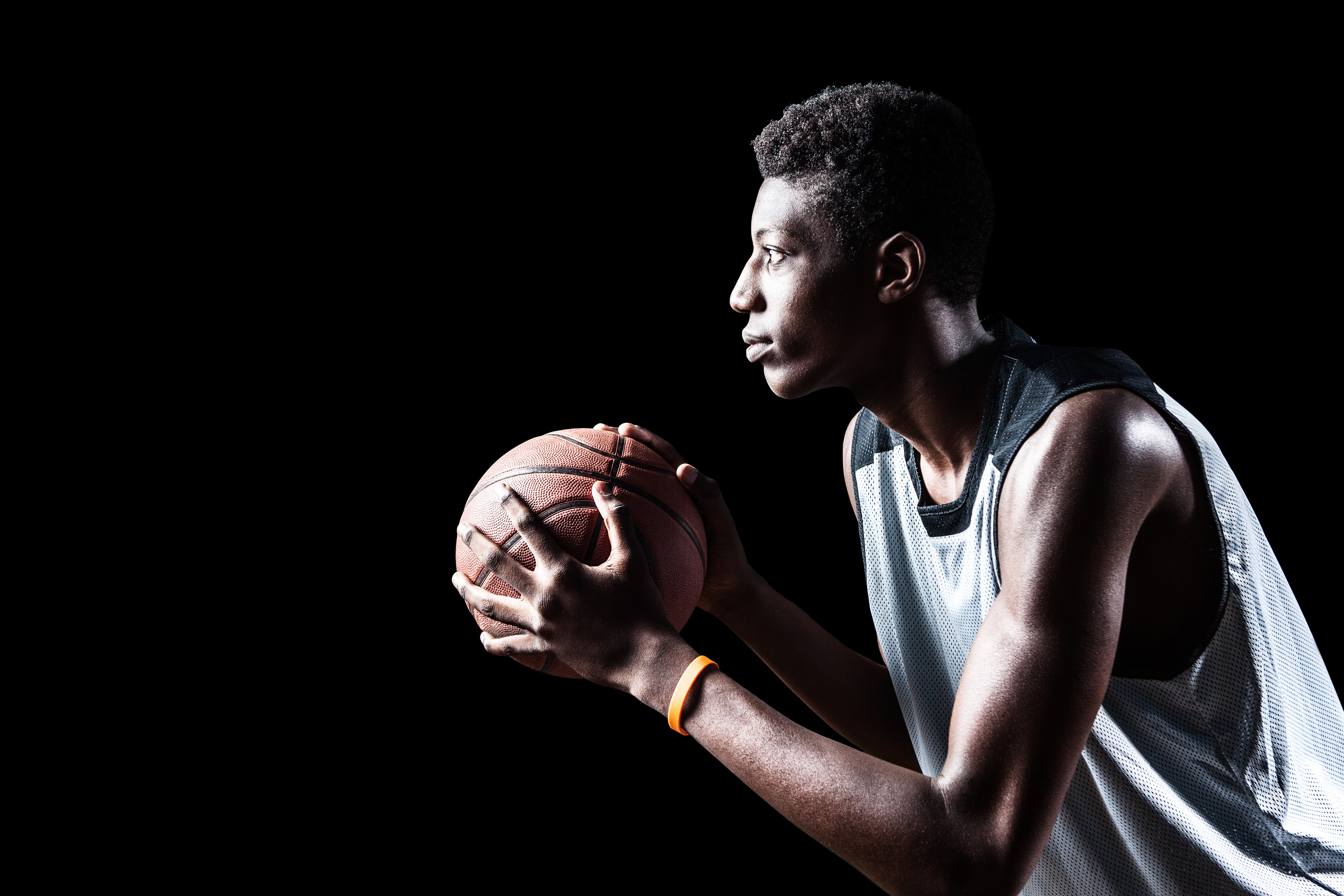 Young basketball player isolated on black background